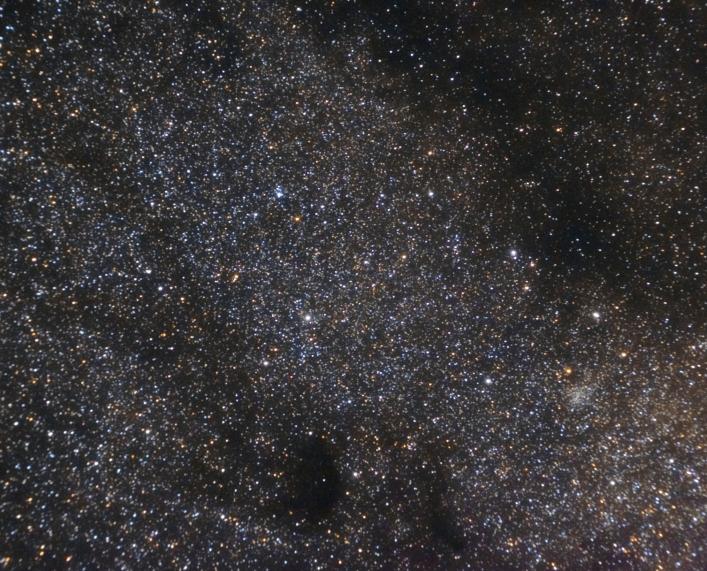 Bulutlarla karışık yıldız görüntüsü, aralarda kara lekeler bulunuyor, bunlar karanlık bulutsuları gösteriyor.