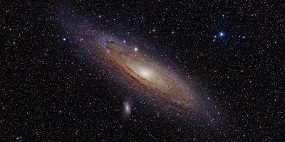Andromeda Galaksisinin fotoğrafı. Ortası parlak ve aydınlık kenarlara ise dalga dalga kollar şekilde yayılan, kenarları mavi ağırlıklı yassı gökada