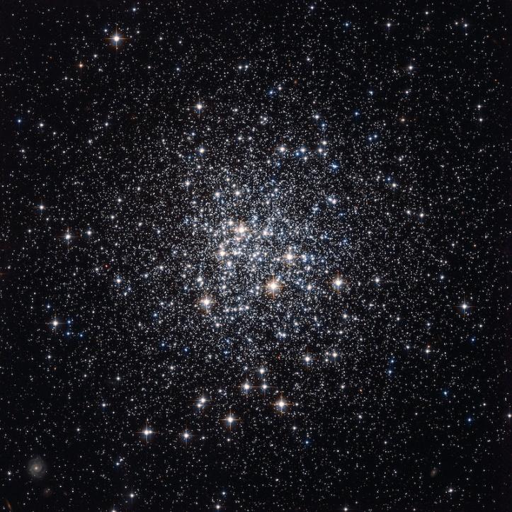 M72 olarak bilinen dağınık yıldızlardan oluşan bu zengin koleksiyon, geceleri bir uçak penceresinden görülen şehirlere benzer; banliyö evlerinden gelen küçük ışık parıltısı, parlak şehir merkezinin eteklerini işaret etmektedir. Messier 72 aslında, küresel bir küme, daha az kentsel alanlara kıyasla bir şehrin kalbindeki binalar gibi, merkezinde birbirine çok daha yakın gruplanmış eski bir eski yıldız koleksiyonu. Fotoğraf, kümenin içindeki çok sayıda yıldızın yanı sıra, küme yıldızlarının arasında ve çevresinde görülen çok daha uzak gökadanın görüntülerini barındırıyor. Fransız gökbilimci Pierre Méchain bu zengin kümeyi 1780 Ağustos'unda keşfetti, ancak yaygın M72 adını, iki ay sonra ünlü kuyrukluyıldızı benzeri nesneler kataloğunda 72. giriş olarak kaydeden Méchain'in meslektaşı Charles Messier'den alıyoruz. Bu küresel küme, Kova (Su Taşıyıcısı) takımyıldızında, Dünya'dan yaklaşık 50.000 ışık yılı uzaklıkta yer almaktadır. Bu çarpıcı görüntü, NASA / ESA Hubble Uzay Teleskobu'ndaki Araştırmalar için Gelişmiş Kameranın Geniş Alan Kanalı ile çekilmiştir. Fotoğraf, sarı ve kızılötesi yakın filtrelerden (F606W ve F814W) çekilmiş imajlardan oluşturulmuştur. Poz süresi, filtre başına yaklaşık on dakika ve görüş alanı genelinde yaklaşık 3.4 yay dakikadır.